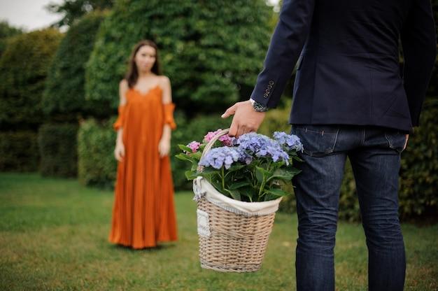 Hombre en traje trae una gran cesta de mimbre llena de flores para una mujer