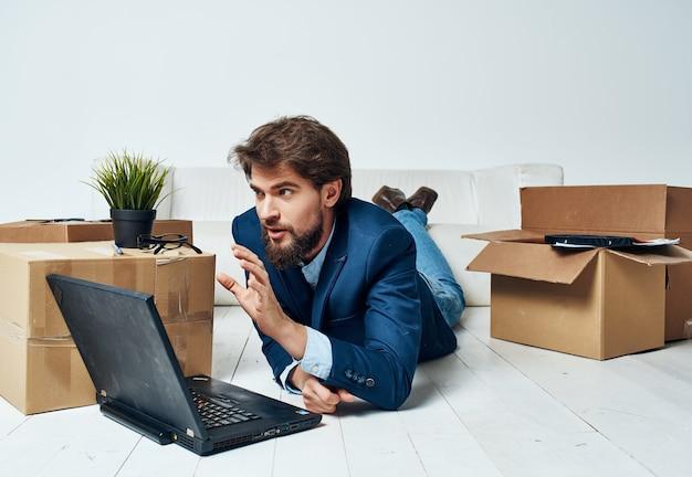 Un hombre con un traje yace en el suelo en cajas con cosas profesionales del administrador de la computadora portátil