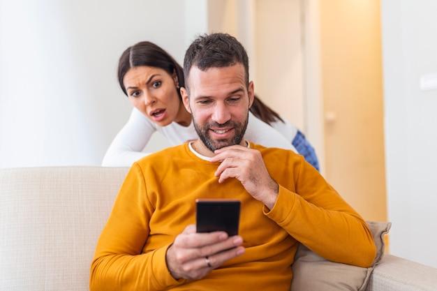 Hombre tramposo que data en línea con un teléfono inteligente y su novia está espiando sentado en un sofá en casa