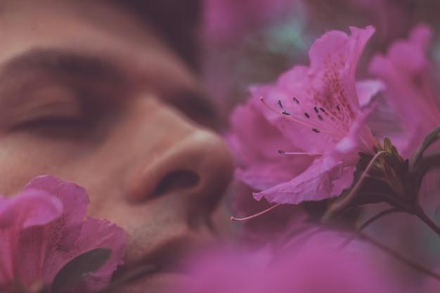Hombre tranquilo guapo con flores en la boca. concepto de personas, emociones, verano o primavera. alergia de primavera. retrato de primer plano de cara.