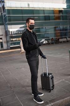 Hombre tranquilo viajando en guantes y máscara protectora
