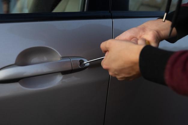 Un hombre está tratando de romper la cerradura del auto para robarlo del estacionamiento.