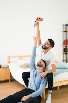 Hombre tratando de tomar el libro de la mano de su novio sentado en la cama
