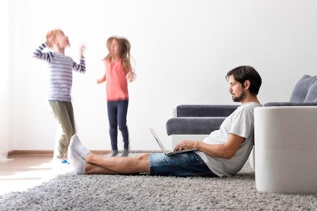 Hombre tratando de trabajar en la computadora portátil desde casa mientras sus hijos corren