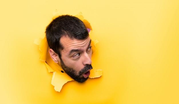 Hombre a través de un agujero de papel
