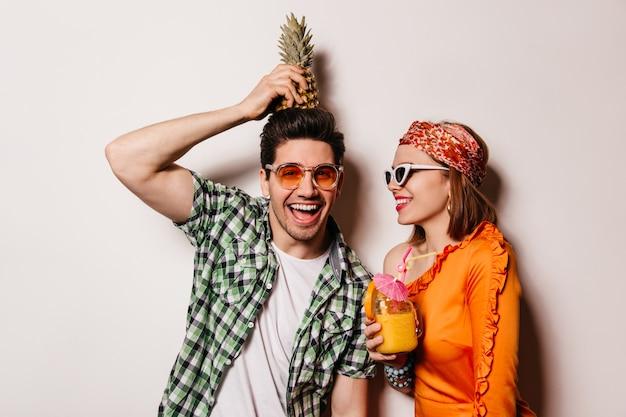 Hombre travieso con camisa verde tiene piña en la cabeza y mira a la cámara con una sonrisa. dama de blusa naranja y vasos con cóctel.