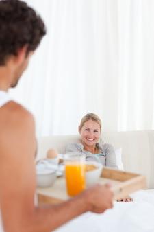 Hombre trayendo el desayuno a su esposa
