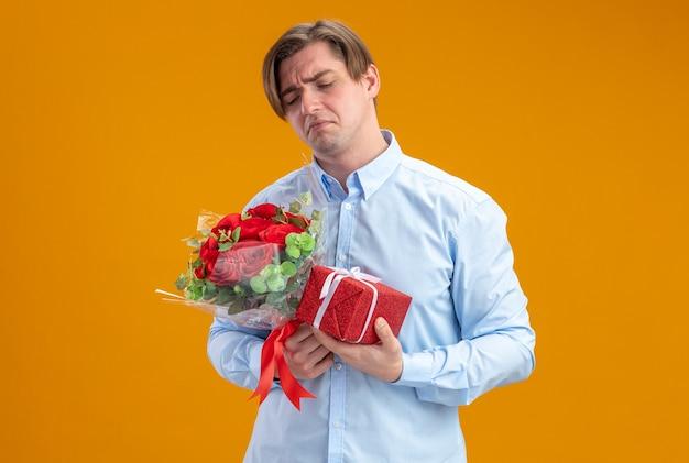 Hombre triste en blueshirt sosteniendo un ramo de rosas rojas y presente frunciendo los labios con expresión decepcionada concepto del día de san valentín de pie sobre la pared naranja