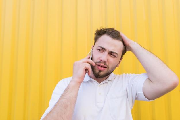 Un hombre triste hablando por teléfono en una pared amarilla. el hombre escuchó las malas noticias por teléfono.