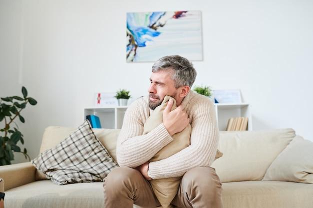 Hombre triste llorando mientras lidia con problemas personales en la terapia