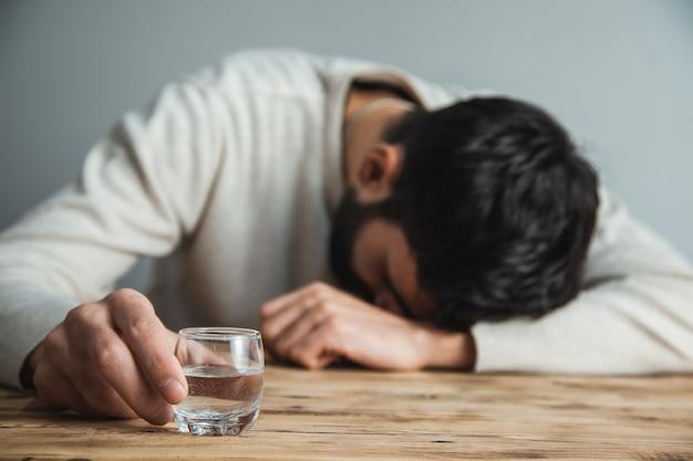 Hombre triste mano vaso de vodka en el escritorio