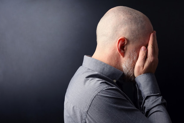 Hombre triste con las manos cerradas la cara se alejó de la luz
