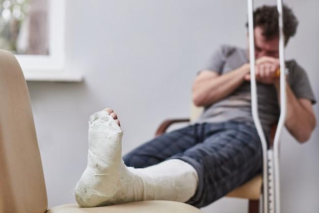 Un hombre triste con una pierna rota se sienta en una silla. concepto de enfermedad.