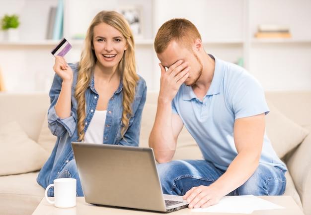 Hombre triste que trabaja con el ordenador portátil mientras que esposa que sostiene la tarjeta de crédito.
