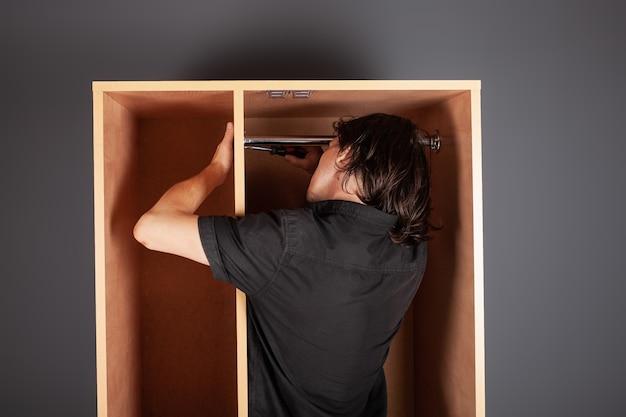 Un hombre tuerce un tubo para colgar en un armario con un destornillador.