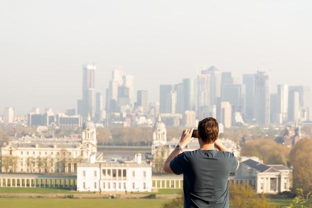 Hombre del turismo que toma la foto de la opinión de la ciudad con el teléfono celular mientras que viaja en verano.
