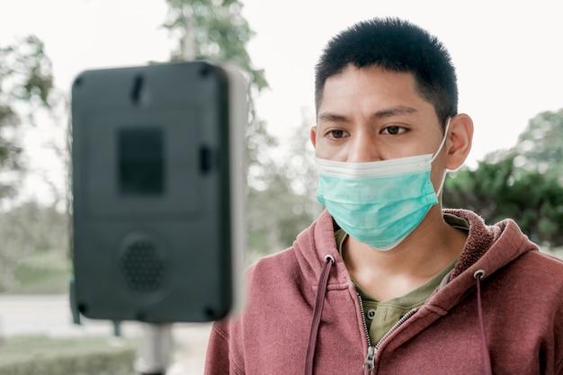Hombre turista asiático ha comprobado la temperatura corporal con un detector de escáner de temperatura térmica