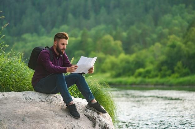 Un hombre turista barbudo, en la orilla de un río de montaña, está estudiando un mapa.