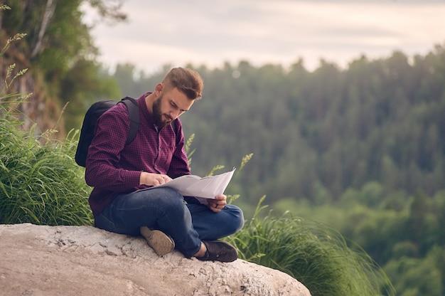 Hombre turista en montaña leer el mapa.
