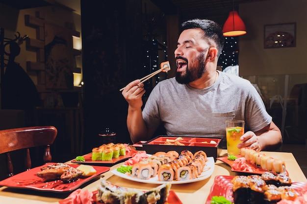 Hombre turístico comer comida asiática calle local café, sonreír con palillos.