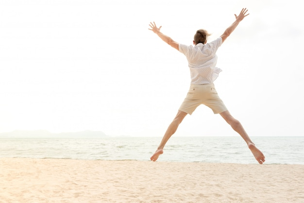 Hombre turístico feliz enérgico joven que salta en la playa