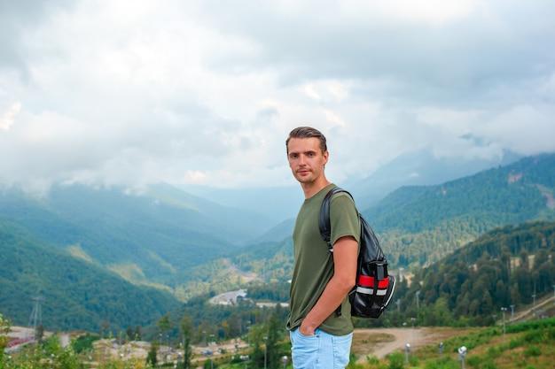 Hombre turístico en montañas en el fondo de niebla