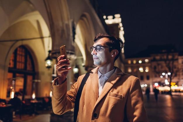 Hombre turístico con smartphone por la noche en la plaza del mercado de cracovia, polonia.