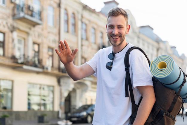 Hombre turístico sonriente sonriendo y saludando