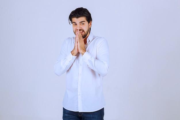 Hombre uniendo sus manos y rezando.