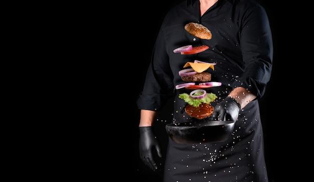 Hombre con uniforme negro sosteniendo una sartén redonda de hierro fundido con ingredientes levitando hamburguesa con queso