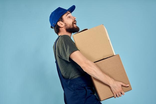 Hombre en uniforme de trabajo con cajas en fondo azul del servicio de entrega de manos.