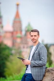 Hombre urbano joven feliz bebiendo café en ciudad europea.