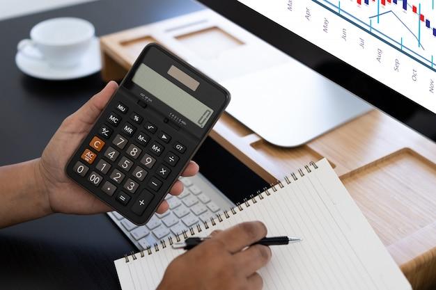 Hombre usa calculadora en escritorio de oficina