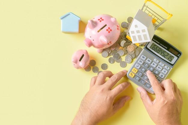 El hombre usa calculadoras para calcular y analizar los gastos financieros.