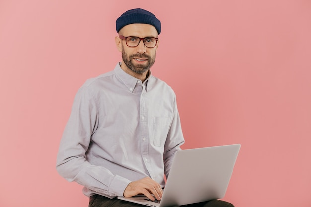 El hombre usa una computadora portátil moderna, se sienta contra el fondo rosa