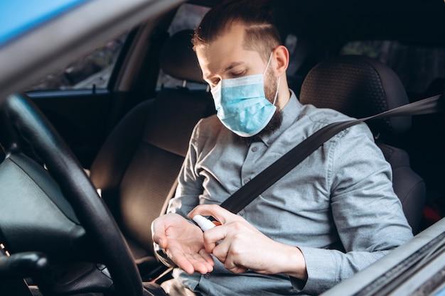 El hombre usa desinfectante mientras conduce un automóvil. precauciones durante la epidemia de coronavirus. hombre en máscara médica en coche.