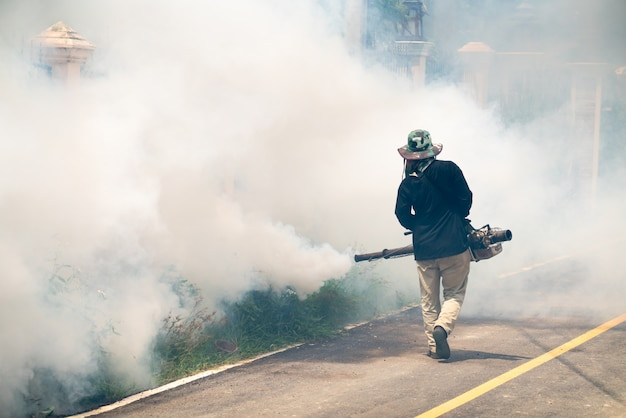 El hombre usa la máquina de mosquitos de fumigación