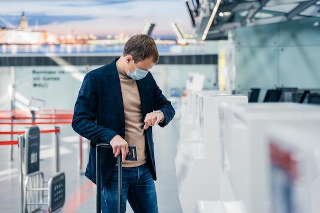 El hombre usa una máscara médica desechable, controla el tiempo en su reloj, posa en el aeropuerto