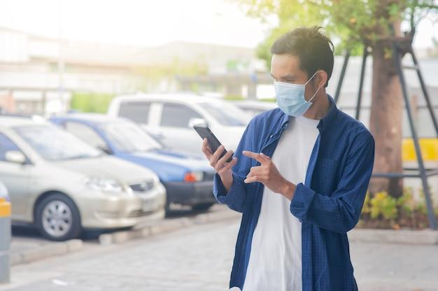 Hombre usa mascarilla con teléfono inteligente móvil