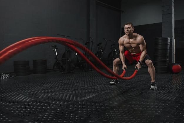 El hombre usa pantalones cortos rojos haciendo ejercicio de cuerdas de batalla en el gimnasio crossfit. el concepto de deporte de motivación. copie el espacio.