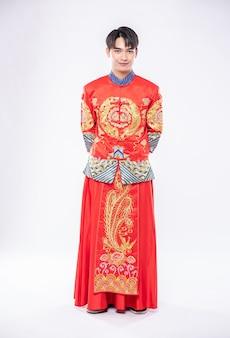 El hombre usa una sonrisa cheongsam para dar la bienvenida al viajero de compras en el año nuevo chino