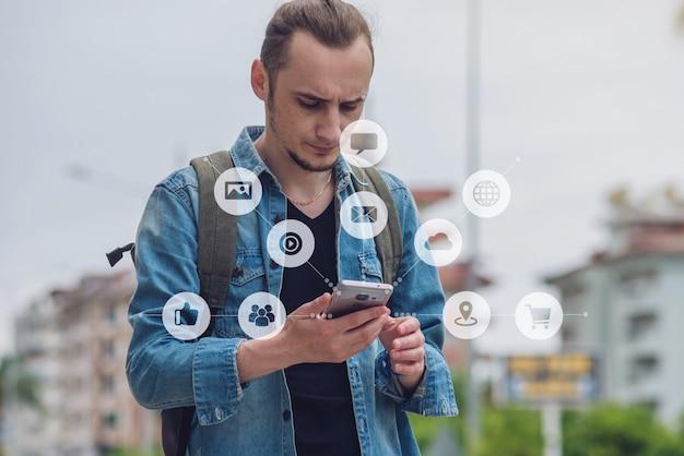 El hombre usa un teléfono inteligente para acceder a las redes sociales digitales en internet