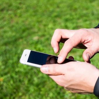 Un hombre usa un teléfono inteligente al aire libre.