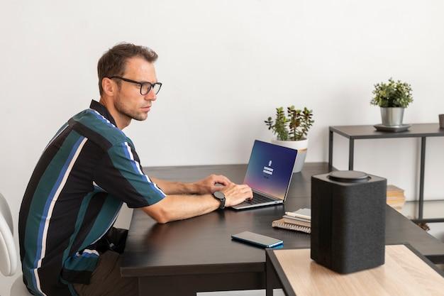 Hombre usando un altavoz inteligente mientras trabaja