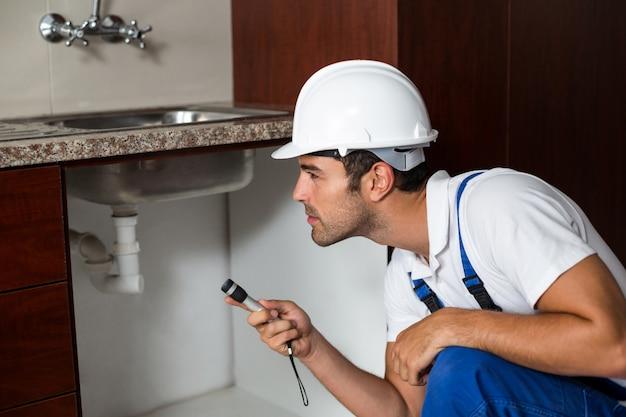 Un hombre está usando una antorcha en la cocina