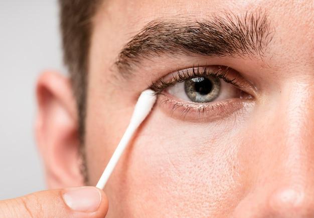 Hombre usando un bastón para la oreja para limpiar su ojo