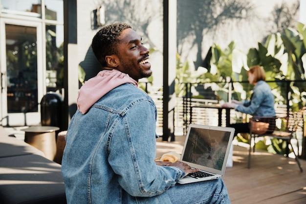 Hombre usando una computadora portátil en un café