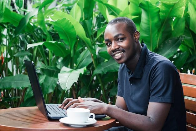 Hombre usando una computadora portátil fuera de un café