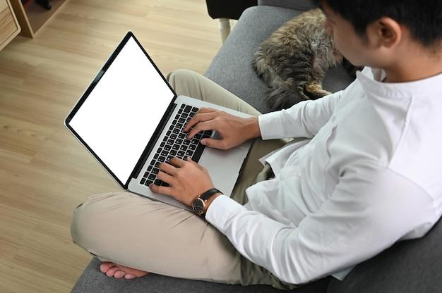 El hombre está usando una computadora portátil con pantalla blanca mientras está sentado en el sofá con su gato