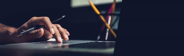 Un hombre usando una computadora portátil trabajando en una nueva idea de proyecto en la oficina a altas horas de la noche